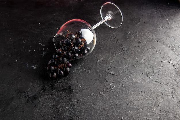 Widok z góry czarne winogrona w przewróconym kieliszku do wina na ciemnym tle