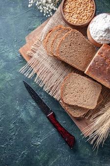 Widok z góry czarnego chleba kromki mąki pszennej na nagim kolorze kolce ręcznika kwiat na deskach do krojenia na tle mieszanych kolorów
