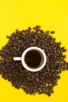 Widok z góry czarnej kawy w białej filiżance i ziaren kawy na żółtej powierzchni