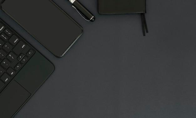 Widok z góry czarny kolor obszaru roboczego z klawiaturą komputerową, smartfonem, długopisem i notatnikiem na czarnym skórzanym blacie.