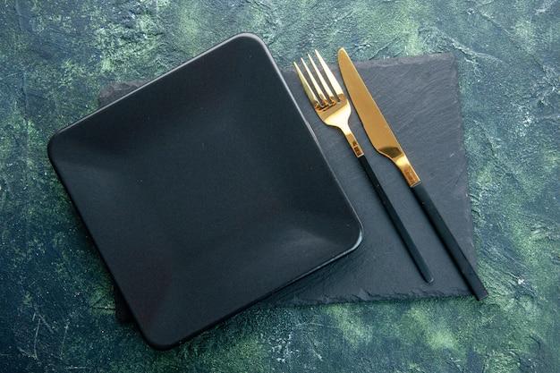 Widok z góry czarny kwadratowy talerz ze złotym widelcem i nożem na ciemnym tle kolor jedzenie restauracja sztućce obiad kuchnia