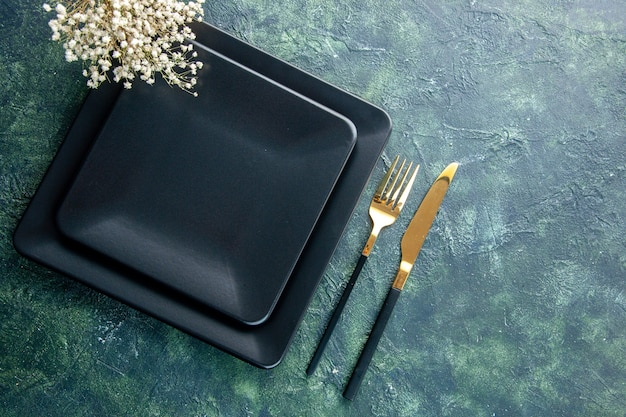 Widok z góry czarny kwadratowy talerz ze złotym widelcem i nożem na ciemnym tle kolor jedzenie sztućce obiad kuchnia restauracja wolne miejsce