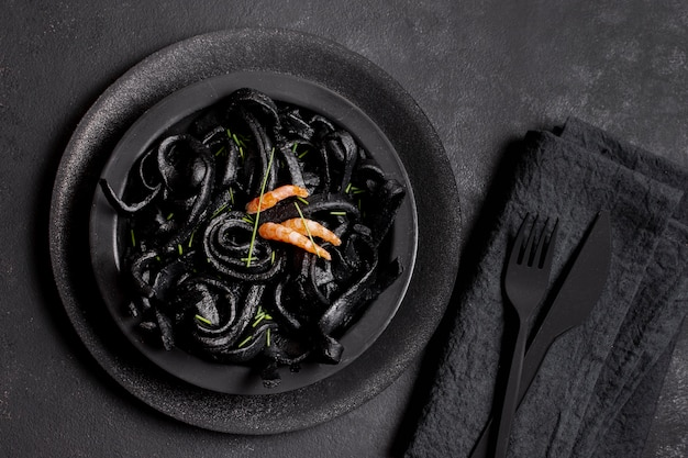 Widok z góry czarny makaron z krewetkami i czarne sztućce