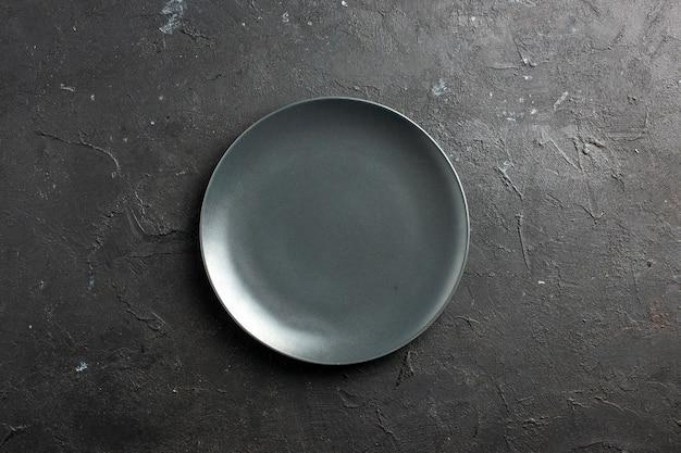 Widok z góry czarny talerz sałatkowy na czarnej powierzchni wolnej przestrzeni
