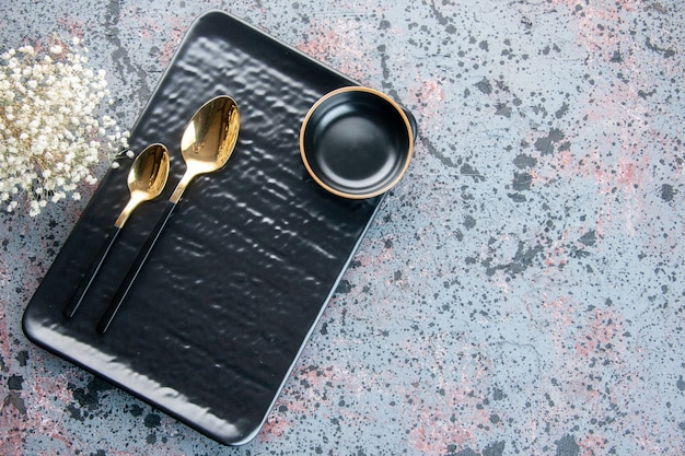 Widok z góry czarny talerz ze złotymi łyżkami na jasnej powierzchni serwis sztućców kolor srebrny taca na jedzenie obiad restauracja