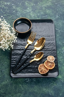 Widok z góry czarny talerz ze złotymi sztućcami na ciemnej powierzchni kolor posiłek obiad srebrne sztućce restauracyjne serwis gastronomiczny