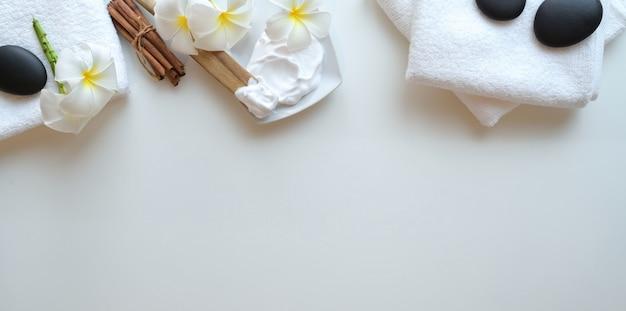 Widok z góry czarnych kamieni i akcesoriów do masażu na białym tle