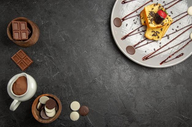 Widok z góry czekolada na stole czekolada i krem czekoladowy po lewej stronie oraz talerz apetycznego ciasta z czekoladą i truskawkami po prawej stronie czarnego stołu