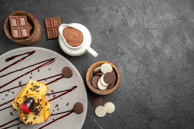 Widok z góry czekolada na stole miski z czekoladą i kremem czekoladowym obok talerza ciasta z truskawkami i czekoladą na stole
