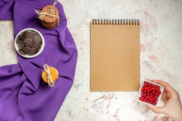 Widok z góry czekolada w misce, ciasteczka związane sznurkiem na fioletowym szalu, miska z jagodami w kobiecej dłoni i notatnik