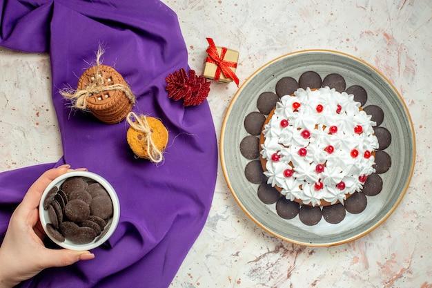 Widok z góry czekolada w misce w kobiecej dłoni ciasteczka związane liną na fioletowym szalu