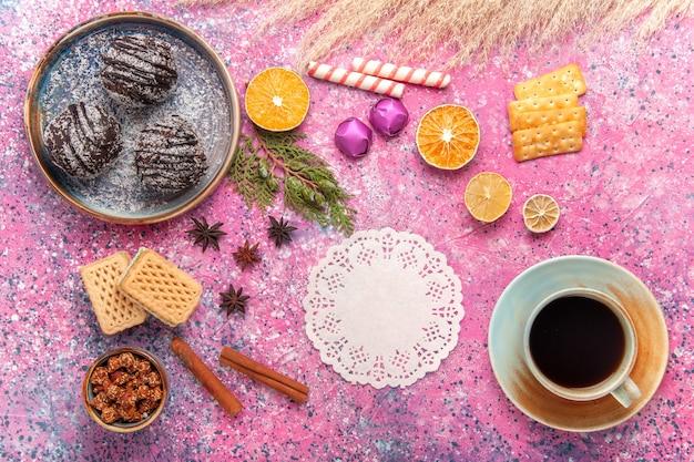 Widok z góry czekoladowe ciasta z goframi i filiżanką herbaty na różowym biurku