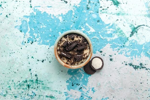 Widok z góry czekoladowe ciasteczka deserowe z kremem i ciasteczkami wewnątrz płyty na niebieskim tle ciasto deser cukier słodki kolor zdjęcie