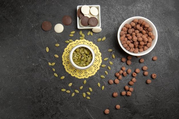 Widok z góry czekoladowe ciasteczka z płatkami piaskowymi pestkami dyni na ciemnym tle kolorowe ciasteczka ciasteczkowe