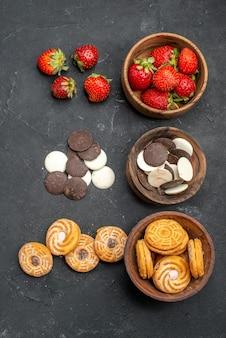 Widok z góry czekoladowe ciasteczka z truskawkami i ciastkami na ciemnym biurku