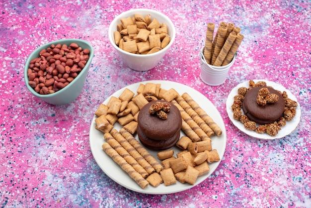 Widok z góry czekoladowe ciastka wraz z ciasteczkami orzeszkami ziemnymi na kolorowym tle ciasteczka herbatniki słodki kolor przekąski
