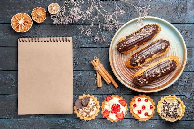 Widok z góry czekoladowe eklerki na owalnym talerzu tarty z suszonymi pomarańczami cynamonowymi i notatnik na ciemnym drewnianym stole