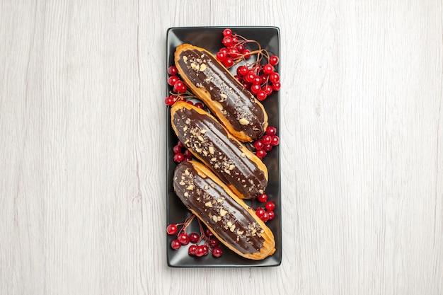 Widok z góry czekoladowe eklery i porzeczki na czarnym pionowym prostokątnym talerzu na białym drewnianym podłożu