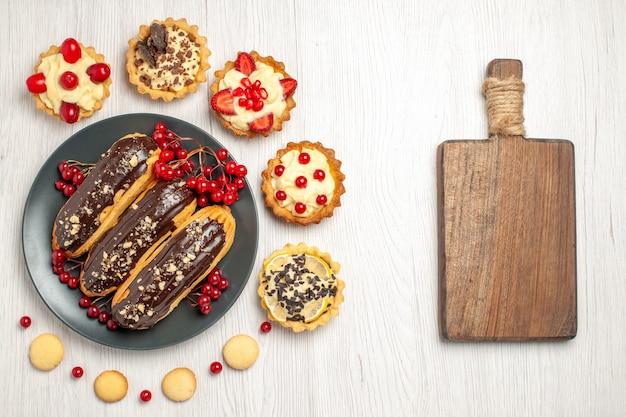Widok z góry czekoladowe eklery i porzeczki na szarym talerzu otoczone tartami i ciasteczkami oraz deską do krojenia na białym drewnianym stole