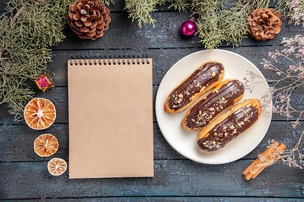Widok z góry czekoladowe eklery na białym owalnym talerzu gałęzie jodły i szyszki świąteczne zabawki suszona gałąź kwiatowa suszone pomarańcze cynamon i notatnik na ciemnym drewnianym stole