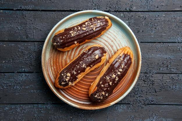 Widok z góry czekoladowe eklery na owalnym talerzu na ciemnym drewnianym stole z wolną przestrzenią