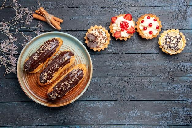 Widok z góry czekoladowe eklery na owalnym talerzu tarty z cynamonem i suszoną gałązką kwiatową na ciemnym drewnianym stole z miejscem na kopię