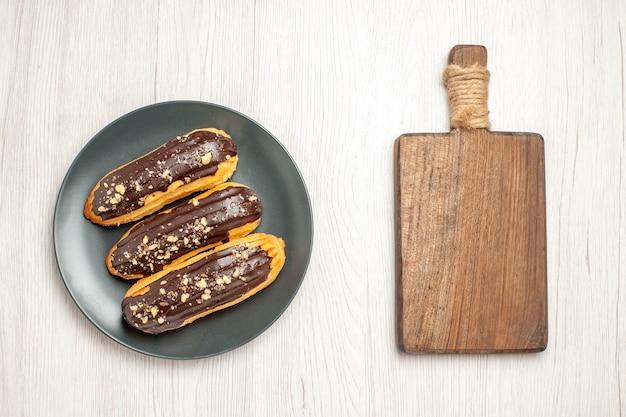 Widok z góry czekoladowe eklery na szarym talerzu i deska do krojenia na białym drewnianym podłożu
