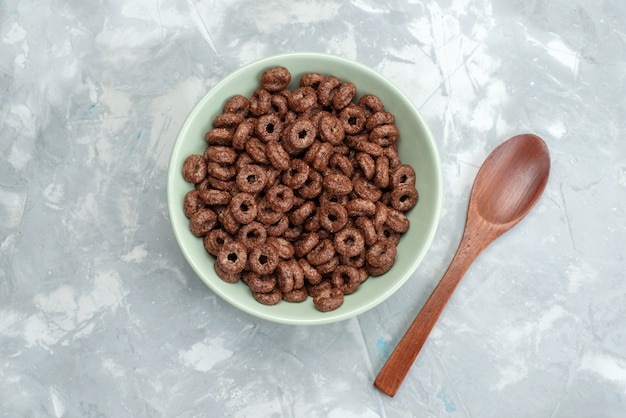 Widok z góry czekoladowe płatki śniadaniowe wewnątrz zielonego talerza wraz z drewnem, łyżką na niebiesko, płatkami śniadaniowymi płatki kukurydziane kakao