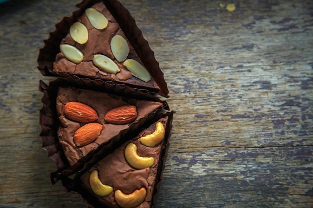 Widok z góry czekoladowego brownie z polewą z migdałów i orzechów nerkowca na zardzewiałym drewnianym stole