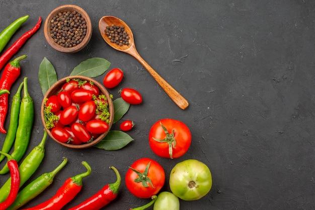 Widok z góry czerwona i zielona papryka i miska pomidorków koktajlowych, czarnego pieprzu i czerwonych i zielonych pomidorów po lewej stronie czarnej powierzchni