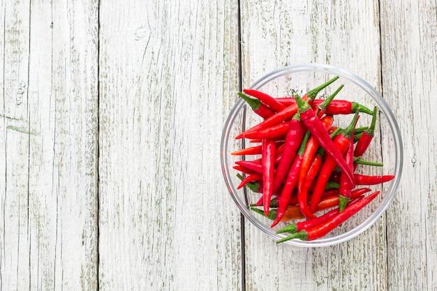 Widok z góry czerwona papryczka chili w przezroczystej misce na białym drewnianym stole.