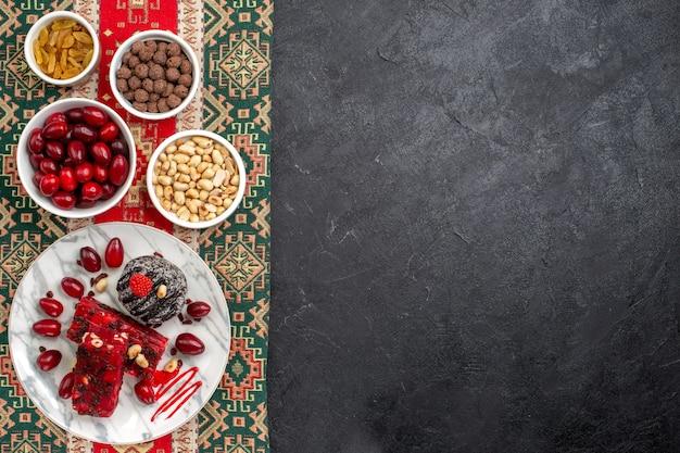 Widok z góry czerwone derenie z nugatem orzechowym i rodzynkami na szarym tle kandyzowanego cukru owoców słodkich orzechów
