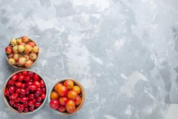 Widok z góry czerwone derenie ze śliwkami wiśniowymi i wiśniami na lekkim biurku