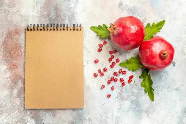 Widok z góry czerwone granaty nasiona granatu notebook na nagiej powierzchni