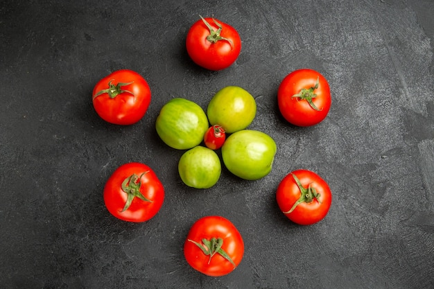 Widok z góry czerwone i zielone pomidory wokół pomidora cherry na ciemnym podłożu z miejsca na kopię