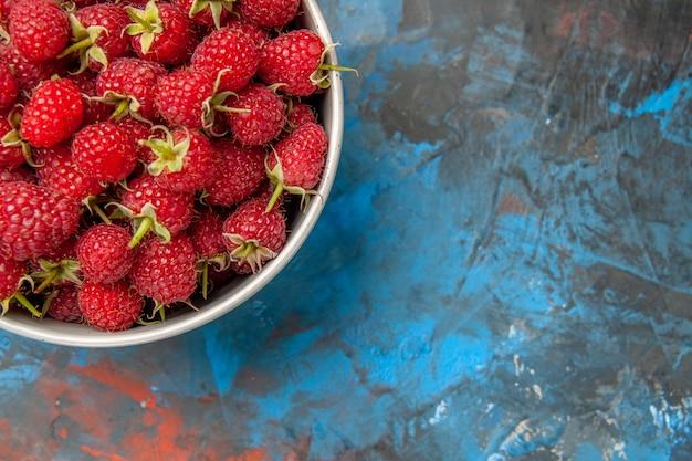 Widok z góry czerwone maliny wewnątrz talerza na niebieskim tle
