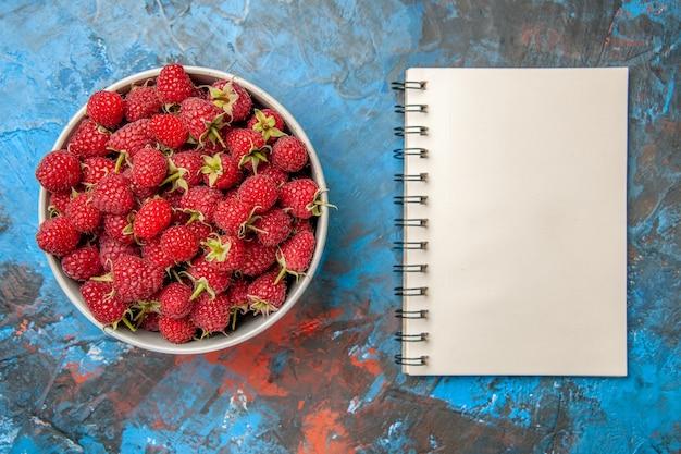 Widok z góry czerwone maliny wewnątrz talerza z notatnikiem na niebieskim tle