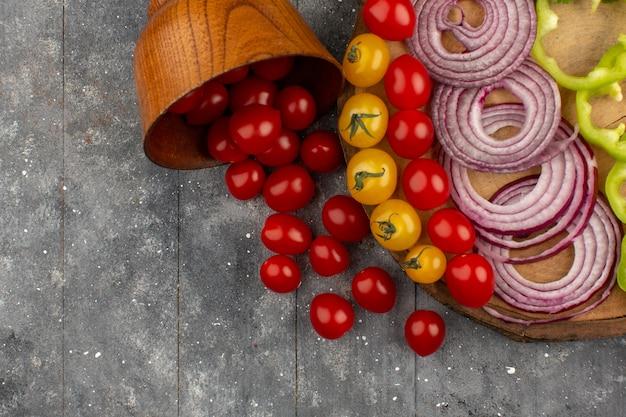 Widok z góry czerwone pomidory z cebulą i zieloną papryką na szarym biurku