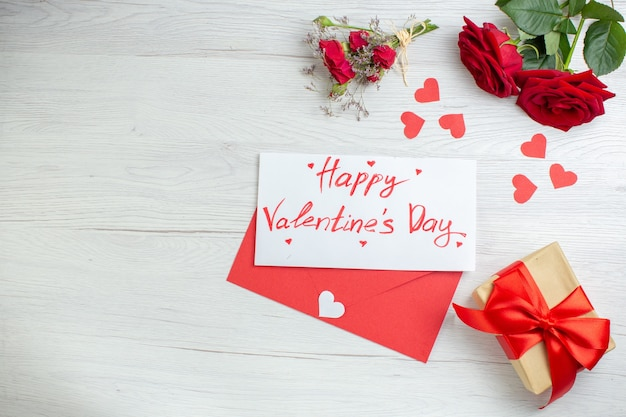 Widok z góry czerwone róże z notatnikiem i prezentem na białym tle miłość wakacje pasja kochanka para małżeństwo serce uczucia uwaga