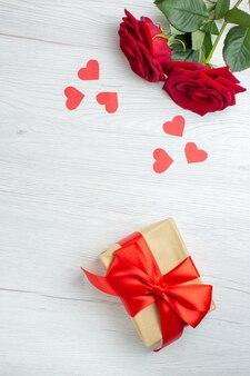Widok z góry czerwone róże z notatnikiem i prezentem na białym tle miłość wakacje pasja kochanka para małżeństwo uczucie uwaga