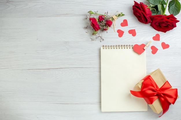 Widok z góry czerwone róże z notatnikiem na białym tle miłość wakacje pasja kochanka para małżeństwo serce uczucia uwaga
