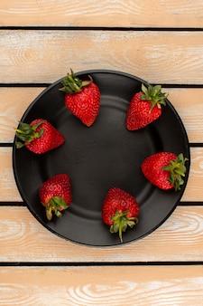 Widok z góry czerwone truskawki całe izolowane wewnątrz czarny talerz na drewnianej podłodze