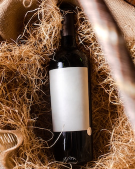 Widok z góry czerwone wino butelka czerwonego wina na sianie
