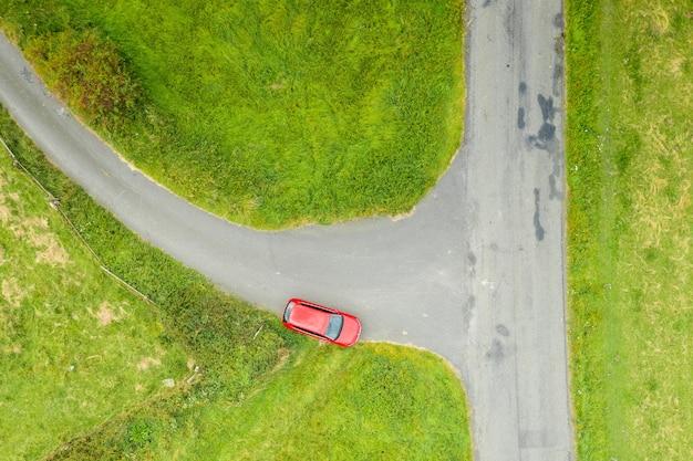 Widok z góry czerwonego samochodu stojącego na skrzyżowaniu w polu