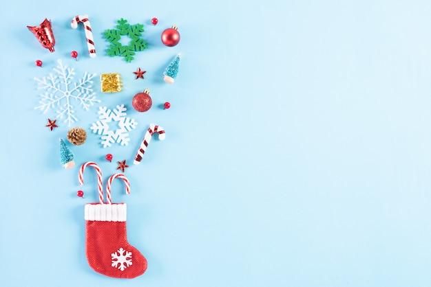 Widok z góry czerwonej skarpety rozchlapać świąteczną dekorację na niebieski pastel.