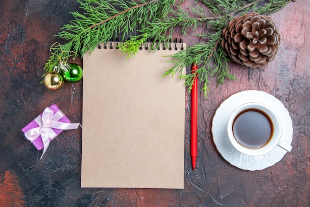 Widok z góry czerwony długopis notatnik gałęzie sosny choinka zabawki i prezenty filiżanka herbaty na ciemnoczerwonej powierzchni
