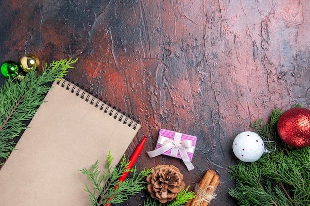 Widok z góry czerwony długopis notatnik gałęzie sosny zabawki choinkowe i prezent cynamon anyż nici słoma na ciemnoczerwonym stole wolne miejsce