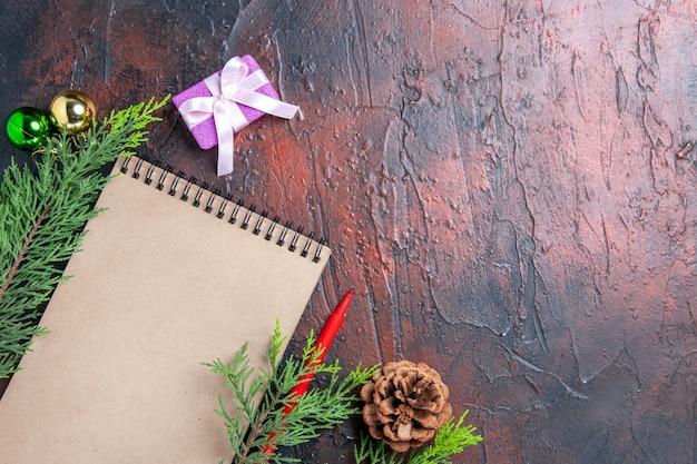 Widok z góry czerwony długopis notatnik gałęzie sosny zabawki kulki choinkowe i prezent na ciemnoczerwonej powierzchni z wolną przestrzenią