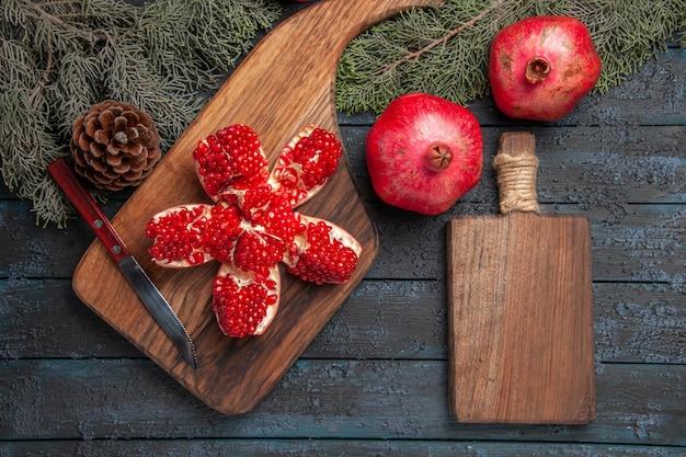 Widok z góry czerwony granat na desce zgnieciony granat na desce do krojenia obok dojrzałych trzech granatów nóż deska kuchenna i świerkowe gałązki i szyszki na stole