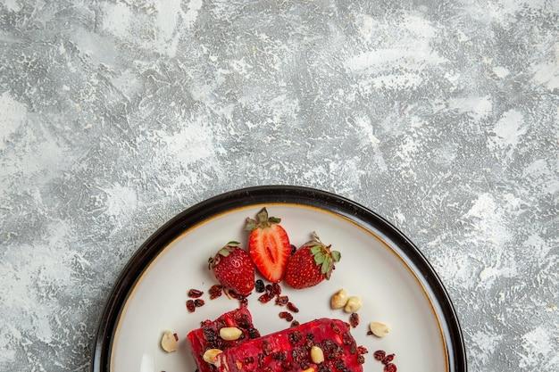 Widok z góry czerwony nugat w plasterkach z orzechami i świeżymi czerwonymi truskawkami na białym biurku